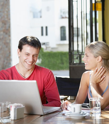 Man and woman in restaurant with laptop smiling : Stock Photo