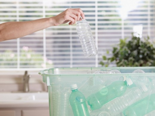 Woman in kitchen putting plastic bottle into recycling bin : Stock Photo
