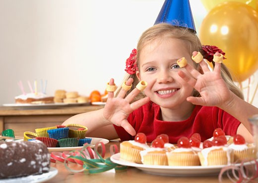 Stock Photo: 1775R-10647 Young girl at birthday party playing with food and smiling