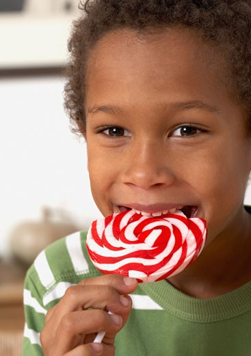Young boy in kitchen biting a lollipop : Stock Photo