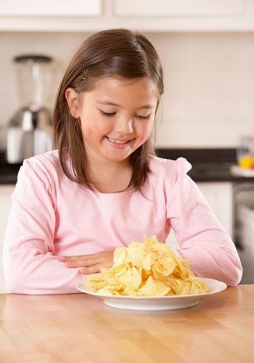 Young girl in kitchen looking at a plate of potato chips smiling : Stock Photo