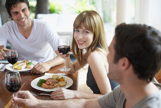 Three people at dinner table talking and smiling : Stock Photo