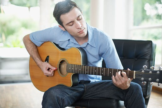 Man sitting in living room playing acoustic guitar : Stock Photo