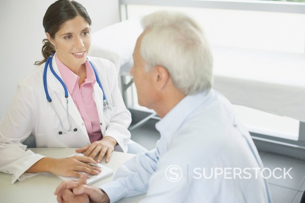Stock Photo: 1775R-10808 Doctor sitting in office with patient talking and smiling