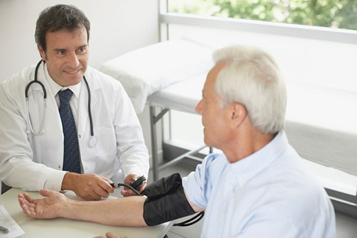 Doctor sitting in office with patient taking blood pressure and smiling : Stock Photo