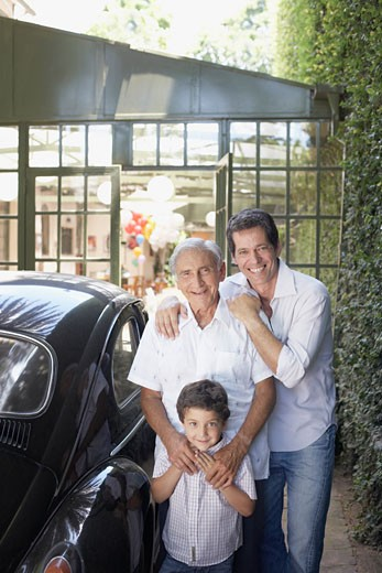 Senior man with man and young boy outdoors standing beside car smiling : Stock Photo