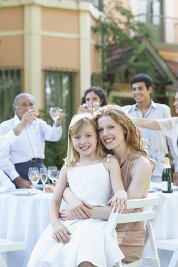 Woman and young girl at outdoor party embracing and smiling : Stock Photo
