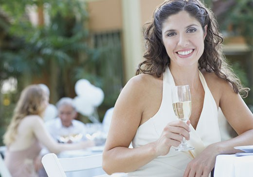 Woman at outdoor party holding champagne and smiling : Stock Photo