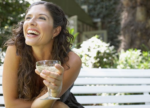 Woman sitting outdoors on bench with white wine smiling : Stock Photo