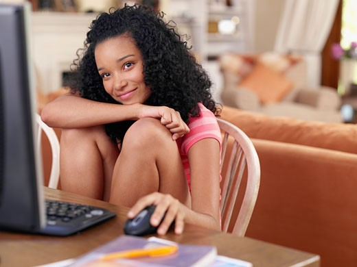 Teenage girl sitting at table with computer : Stock Photo