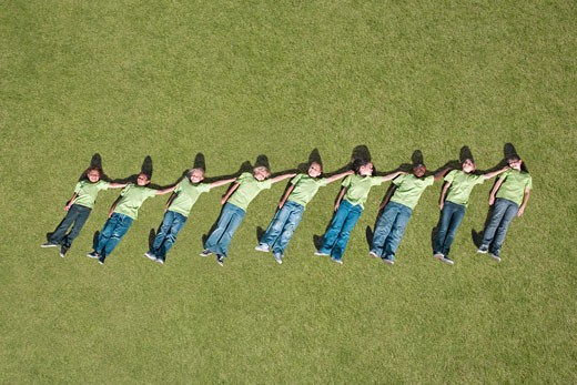 Stock Photo: 1775R-11209 Group of children laying in grass in height ascending order