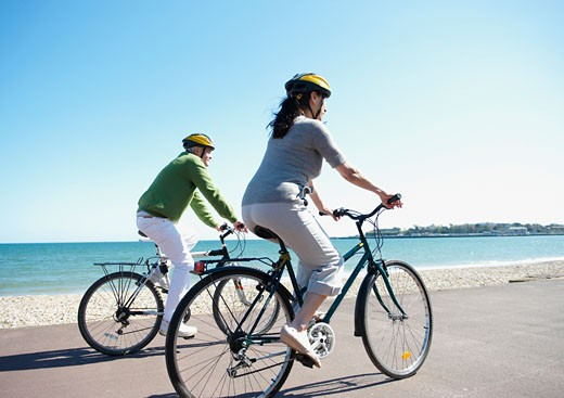 Couple riding bicycles on beach : Stock Photo