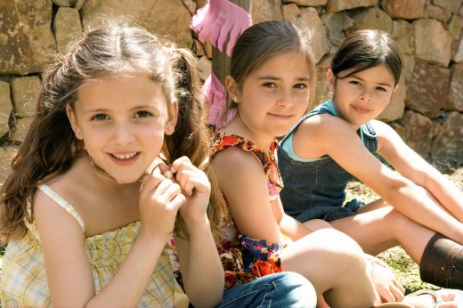 Three young girls sitting outdoors : Stock Photo