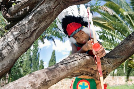 Stock Photo: 1775R-11321 Young boy in indian costume aiming bow and arrow
