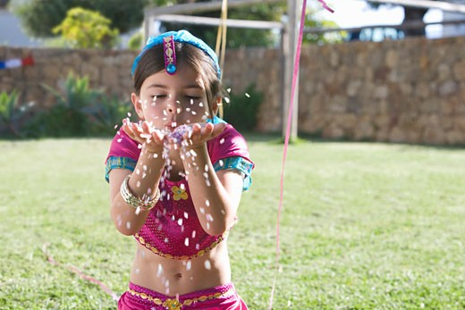 Young girl in costume blowing confetti : Stock Photo