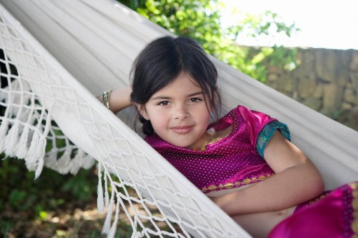 Stock Photo: 1775R-11355 Young girl in costume sitting in hammock