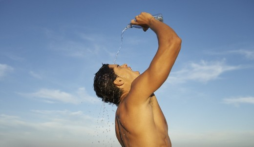 Stock Photo: 1775R-1138 Man on a beach pouring water from a bottle over himself
