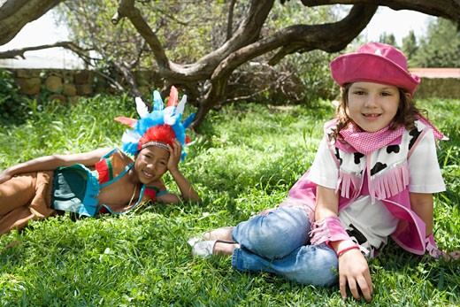 Boy and girl in cowgirl and indian costumes : Stock Photo