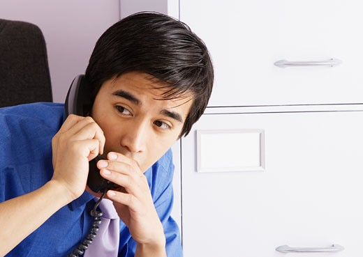 Stock Photo: 1775R-11424 Businessman whispering into telephone