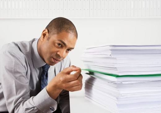 Businessman removing document from stack of paperwork : Stock Photo