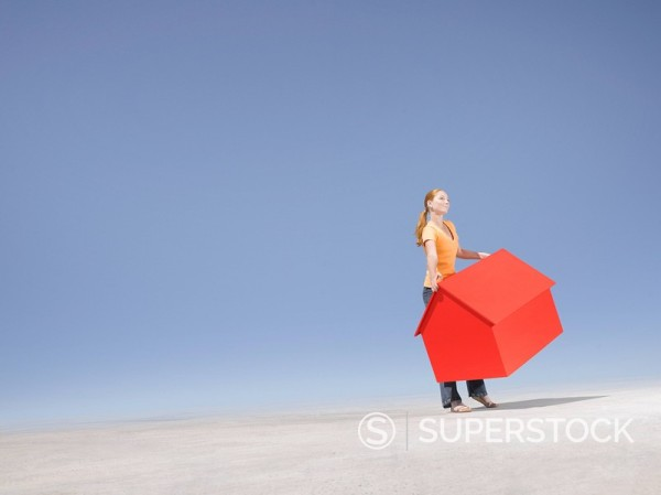 Stock Photo: 1775R-11624 Woman holding small model house in desert