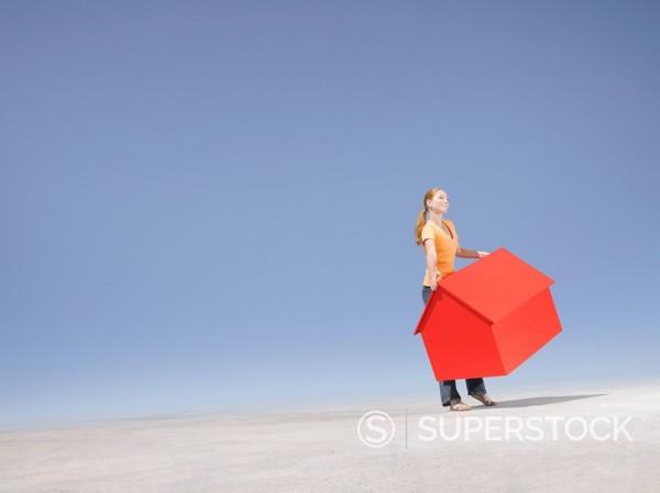 Woman holding small model house in desert : Stock Photo