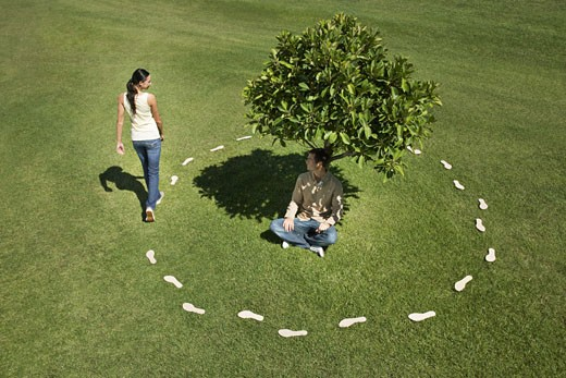 Woman trailing footprints walking around man under tree : Stock Photo