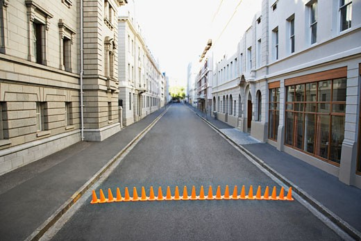Line of traffic cones in urban roadway : Stock Photo