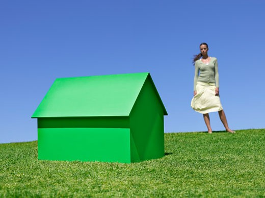 Stock Photo: 1775R-11846 Woman standing near small model house