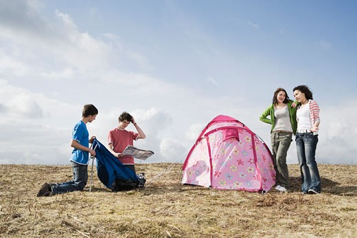 Teenage couples camping in field : Stock Photo