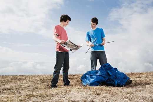 Teenage boys putting up tent : Stock Photo