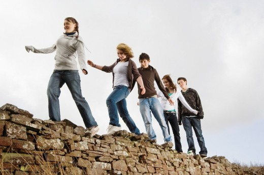Teenage friends walking along rock wall : Stock Photo