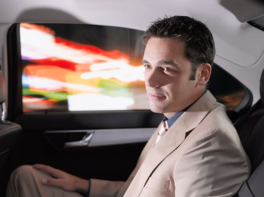 Businessman sitting in back seat of car : Stock Photo