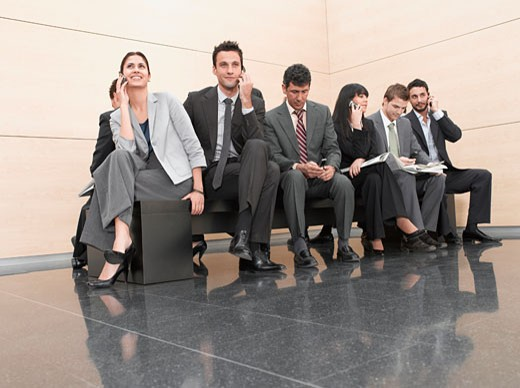 Businesspeople sitting on crowded bench : Stock Photo