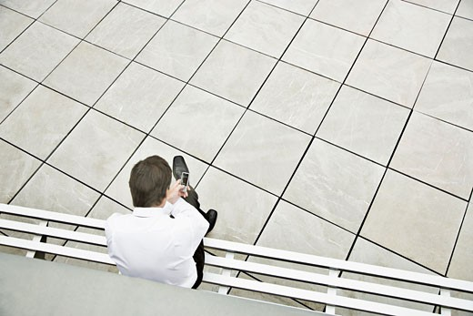 Businessman talking on cell phone in courtyard : Stock Photo