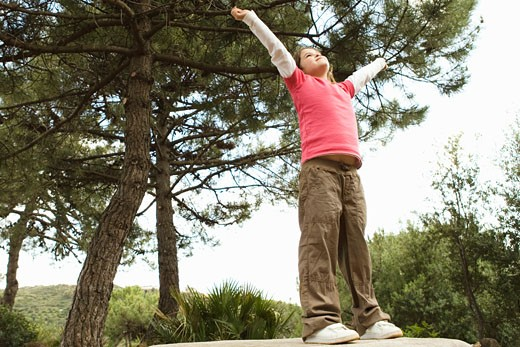 Girl standing on rock with arms outstretched : Stock Photo