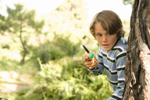 Stock Photo: 1775R-12541 Boy with walkie talking hiding behind tree