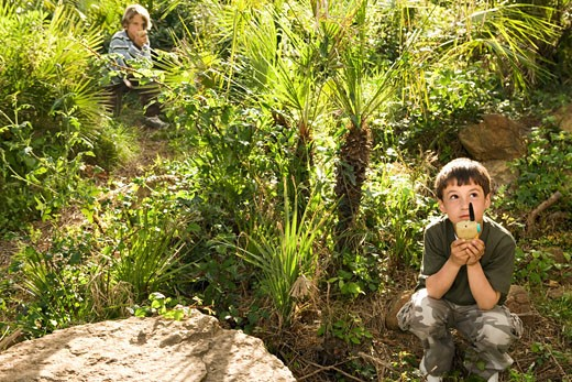 Boys using walkie talkies in lush park : Stock Photo