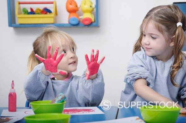 Girls finger_painting in classroom : Stock Photo