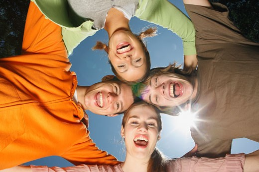 Low angle view of friends huddling outdoors : Stock Photo