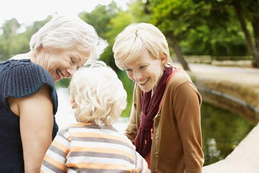 Grandmother, mother and son sitting near pond : Stock Photo