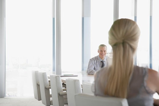 Businesspeople sitting at conference table : Stock Photo