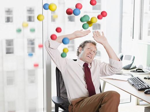 Balls being thrown at businessman : Stock Photo