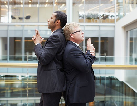 Businessmen fighting symbolic duel : Stock Photo
