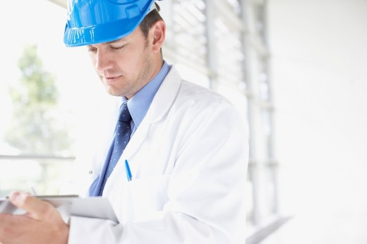 Businessman in hard_hat writing on clipboard : Stock Photo