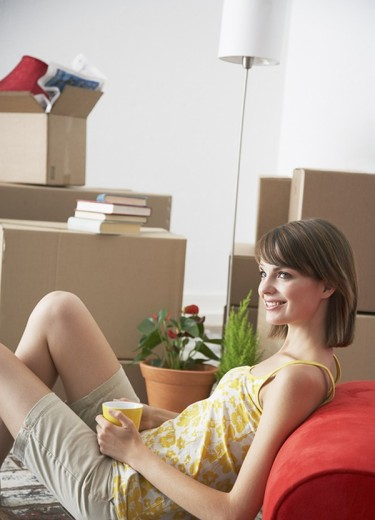 Woman sitting on hardwood floor with mug and cardboard boxes smiling : Stock Photo