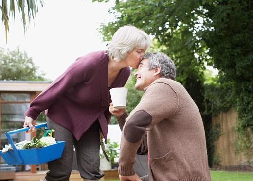 Senior woman kissing husband : Stock Photo