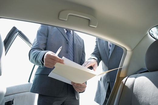 Businessmen reviewing paperwork near car : Stock Photo
