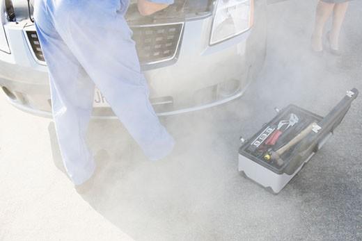 Mechanic checking smoking car engine : Stock Photo