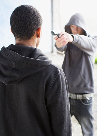 Attacker pointing gun at man : Stock Photo